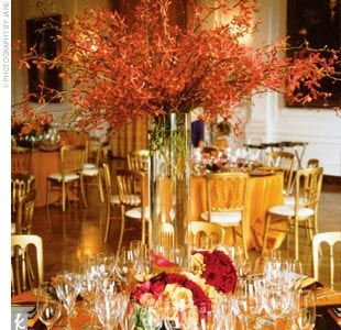 These tall centerpieces showcase burnt-orange orchid sprays, roses, calla lilies, and persimmons around the base.