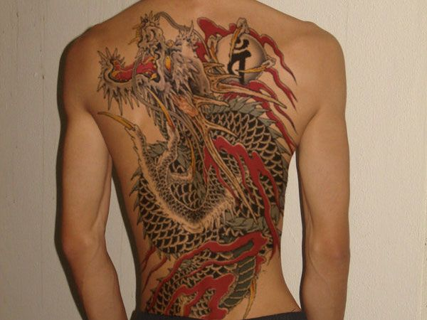 Fierce Dragon With A Kanji Symbol In Its Claws Tattooed On His Back