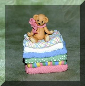 Miniature bear on a stack of blankets by Manda Theart.