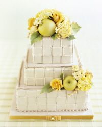 Clusters of darling green marzipan apples and yellow sugar roses and mums adorn square tiers, covered with pale-mocha frosting in a woven motif.