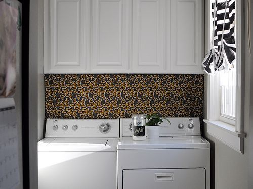 Hang a piece of fun fabric from the bottom of my shelf to behind the washer and dryer to cover up the outlets.  Fun, pop of modern- check, hide ugly outlets- check.  Genius!