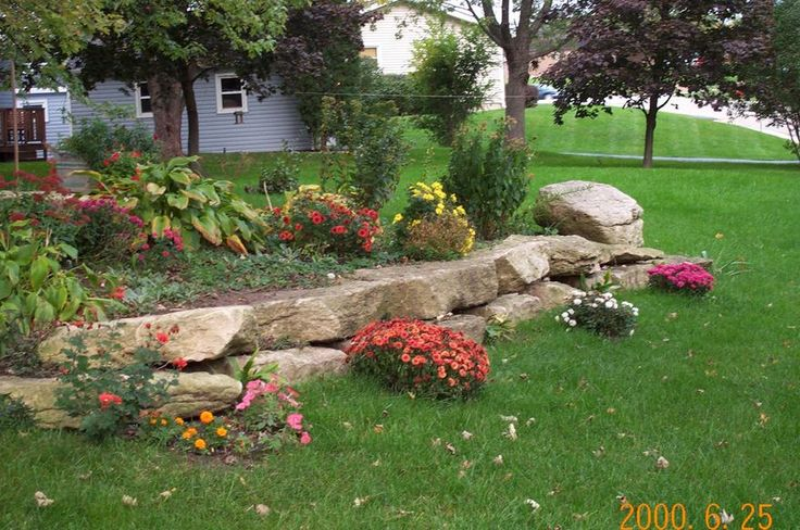 Rock landscape around flower beds in my dream home for Rock flower bed ideas