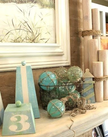 diy beach summer mantle- The balls are painted christmas ornaments wrapped in twine. Our local Dollar Tree carries the lighthouse cutout. The Pylons are pool noodles wrapped  with wood print contact paper!