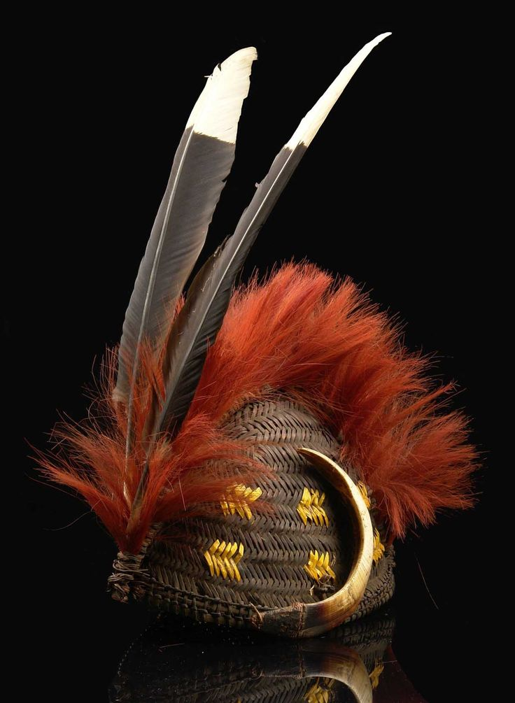 India | Ceremonial headdress of a Naga warrior | Plaited rattan, dark brown with patterns in between dyed in yellow, a crest of red dyed goat' s hair across the headdress and at its front end two calao feathers stuck into a small splinter, boar tusks attached on either side, rattan chin strap | 800€ ~ Sold