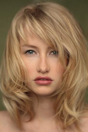 Medium length wavy layered blonde with side swept wispy bangs hairstyle