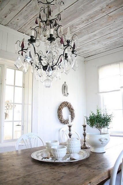 scrubbed wood table, sparkling chandelier and white china