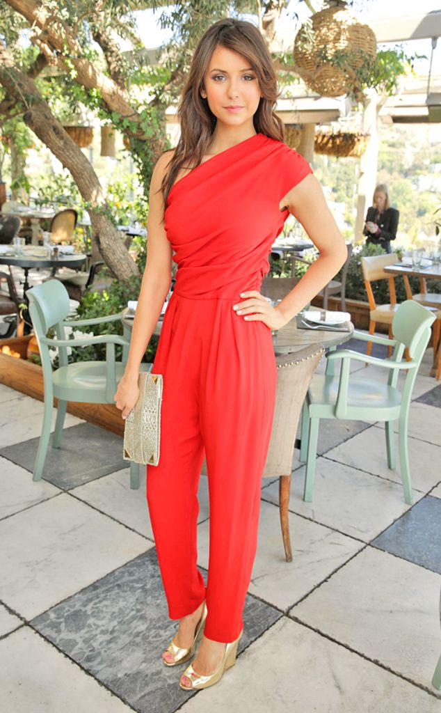 Nina Dobrev stands out in a ravishing red one-shoulder MaxMara jumpsuit.
