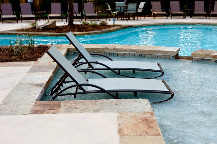 Chaise lounge chairs in pool water