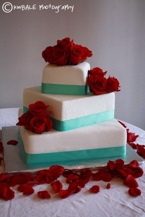 Red roses and petals, white cake, and blue ribbon - a beautiful combination! Roses and rose petals are available year-round at GrowersBox.com.