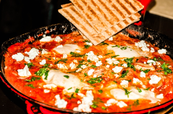 Shakshouka is a dish of eggs poached in a tomato sauce mixture ...