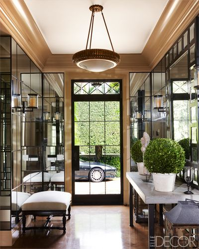 A 19th-century English stool and mirrored paneling in the entry of this Palm Beach home.