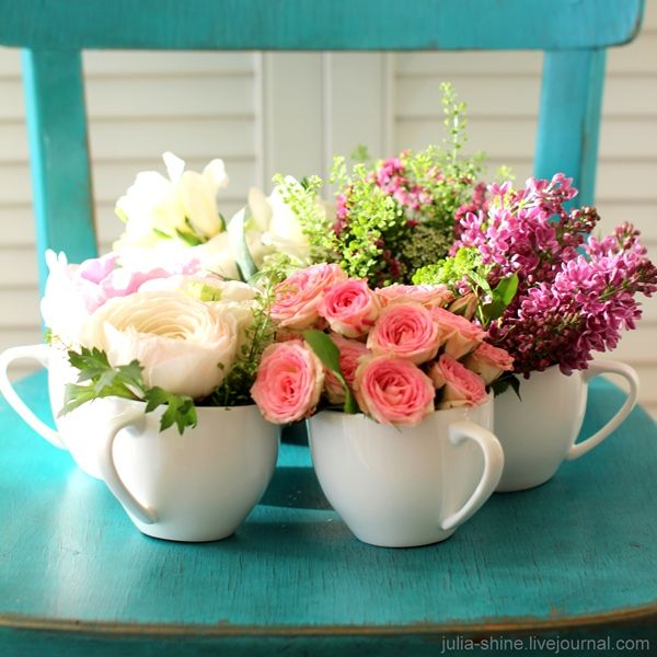 Colorful flowers in white teacups