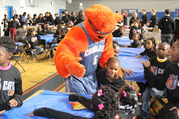 Rufus spending time with children at the Kids Cafe Dinner on Cats Care Day of Service