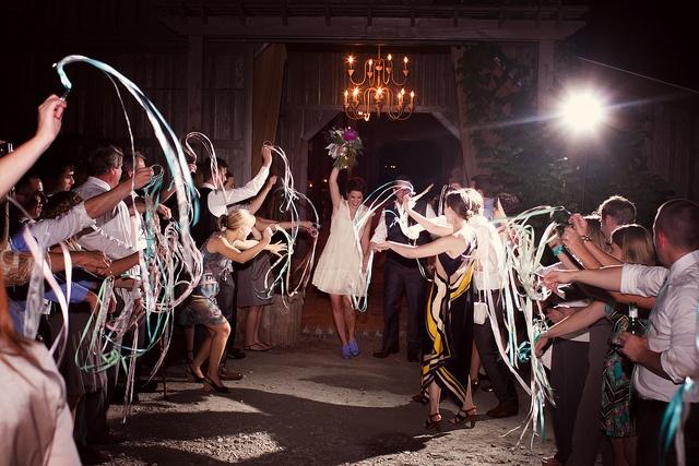 Our wedding exit, by http://seanandamanda.com @Vinewood Weddings & Events #barn #chandelier #ribbon #bride #groom #blueshoes