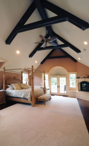 vaulted ceiling bedroom with french doors beams and ceiling fan