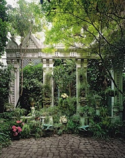 """Tony & Elizabeth Duquette tiny garden in San Francisco: As Wilkinson recalls, """"Tony made a decorative screen across the back of the garden from discarded Victorian architectural elements that he picked off demolition sites in the neighborhood. He paved the garden with old cobblestones torn up from San Francisco streets and planted it with succulents and bromeliads in variegated shades of green. It was a magical shady space to sit or dine in, or just to look out over from the upper floors."""