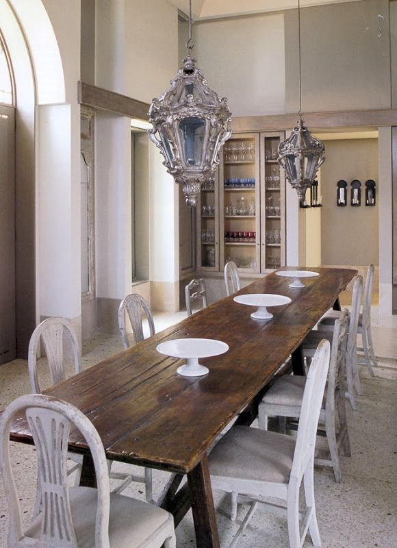 "A narrow farmhouse table and milk painted chairs from the ""Belgian Pe"