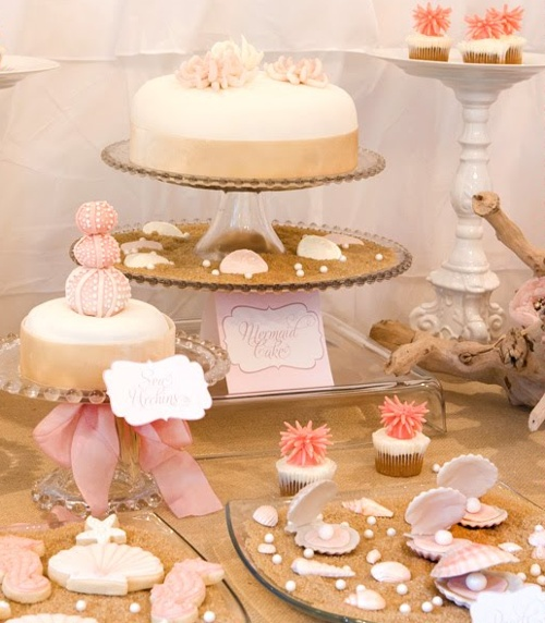 A mermaid-themed party automatically brings forth mental imagery of Disney's Ariel, Sebastian, bright reds and aqua shades. I was pleasantly surprised when I came across this mermaid party with its soft pinks, pearly whites, and sandy arrangements.