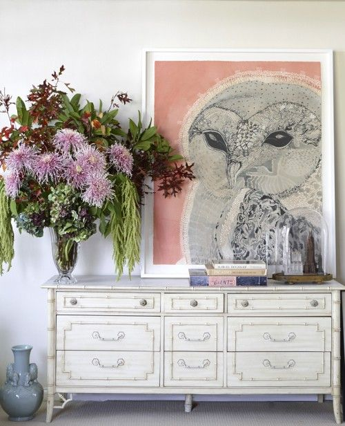 """""""This is an incredible 1950s egg shell bamboo Italianate credenza in my living room,"""" Alex says. """"The large-scale original Owl artwork is by Joshua Yeldham. It looks divine hanging over the decadent flowers by the master Sean Cook. Under the dome is a cityscape of New York City made via a collection of old architectural buildings collected over time."""""""