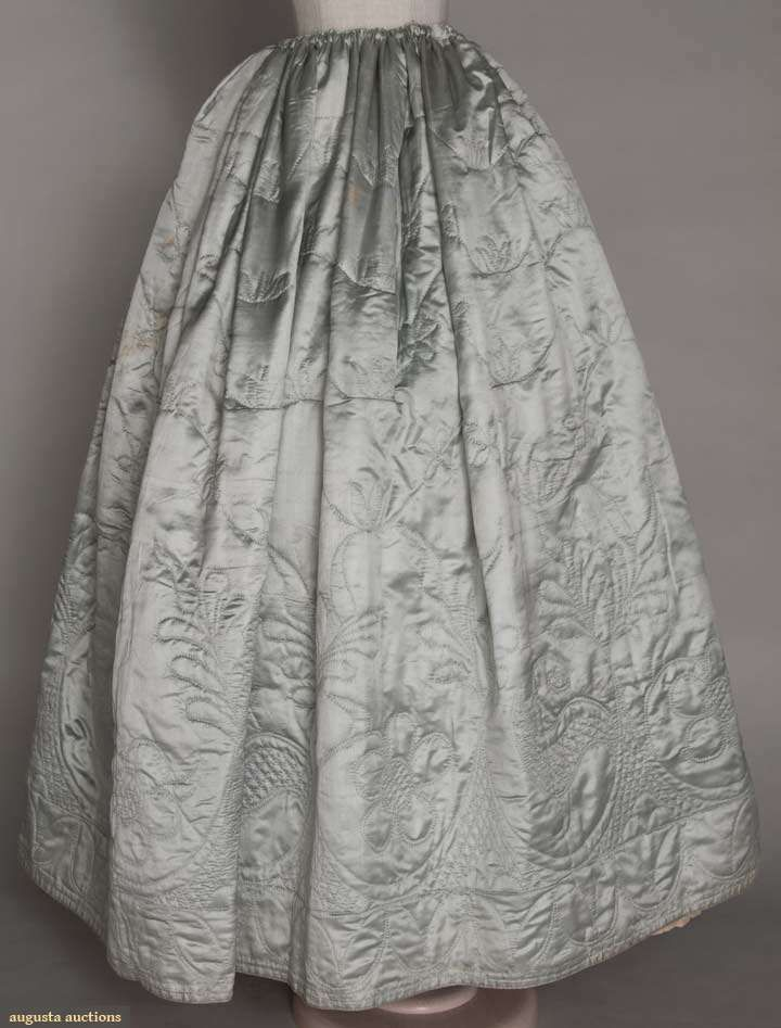 """QUILTED SILK PETTICOAT, 1770-1780s  Baby blue silk satin, draw-string waist, cream calamanco lining, quilted in patterns of tulips at hem w/ larger pattern of 5 petal flowers, stylized leaves & fronds w/in scallops above, from waist to knee sparse pattern of serpentine vines w/ small flowers, W 26""""-50"""", L 38"""", (brown stains around right pocket slit) very good. BROOKLYN MUSEUM"""