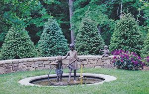 Pond, sculpture and evergreen trees for a designer showcase in NJ.