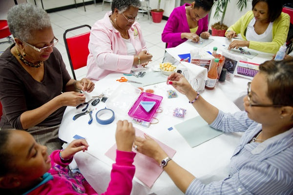 From left, Nala Booze, Beaula McCoy, Brenda Williams, Kayla Booze, Atika Booze, and Shatara Williams make jewelry before dinner in New Orleans, Feb. 7, 2012. Shatara, Beaula, and Brenda are all mentors paired with the Booze sisters through Mentoring Children of Prisoners. Full story: http://www.csmonitor.com/The-Culture/Family/2012/0325/No-child-left-alone-Volunteers-mentor-children-of-inmates