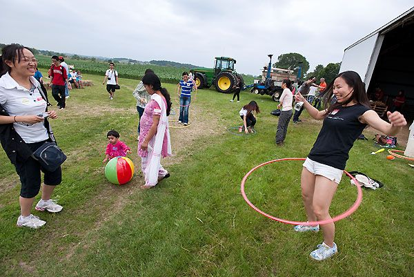 Dee Lei laughs as Zilin Zhu, both from China, takes a hula hoop whirl