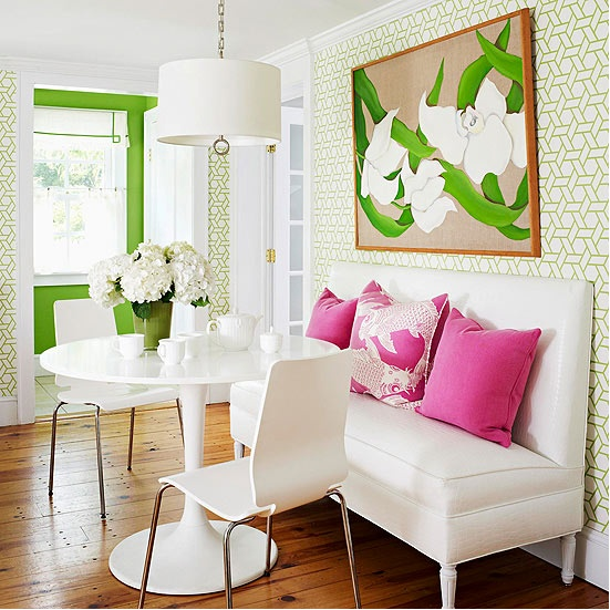 Colorful breakfast nook.  Green trellis wallpaper, green accent wall, and hot pink pillows.