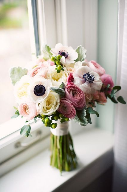 Bouquet of ranunculus, garden roses, anemones, with hypericum berries and dusty miller