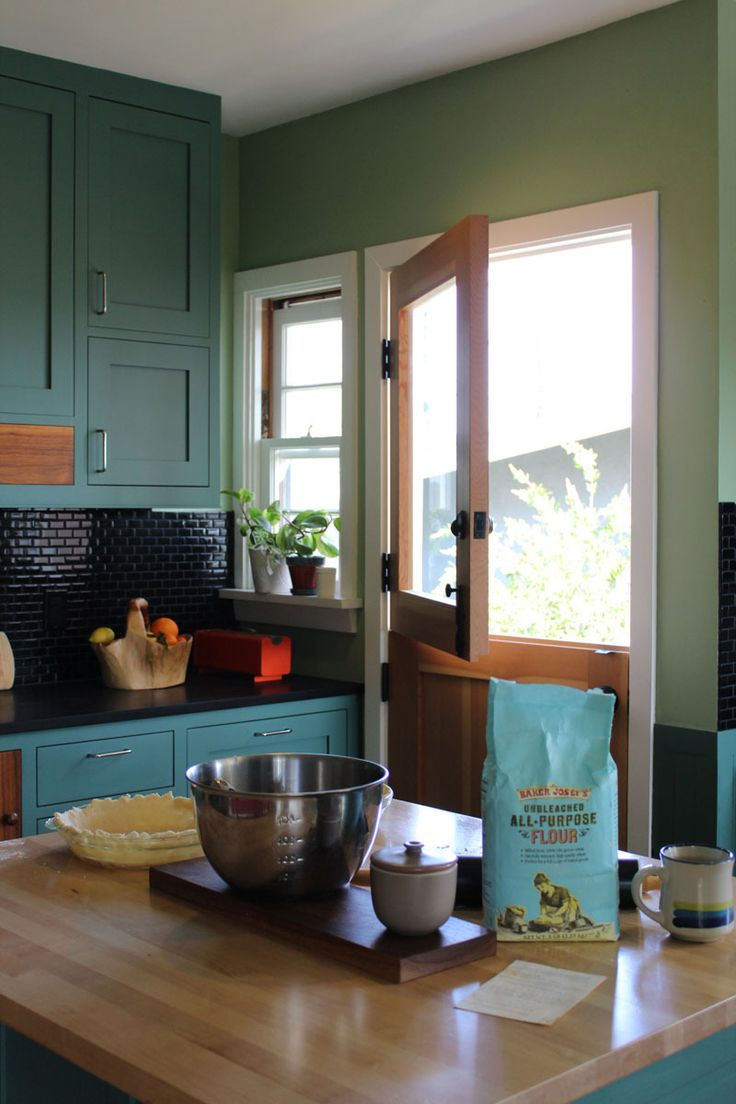 Teal kitchen with dutch doors, island, and good lighting