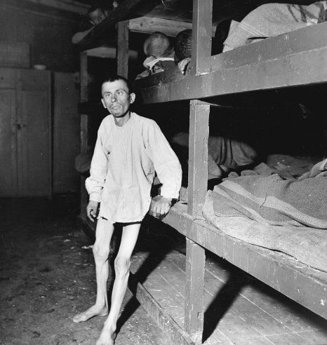 """The caption that accompanied this image when it appeared in the May 7, 1945, issue of LIFE: """"Deformed by malnutrition, a Buchenwald prisoner leans against his bunk after trying to walk. Like other imprisoned slave laborers, he worked in a Nazi factory until too feeble."""""""