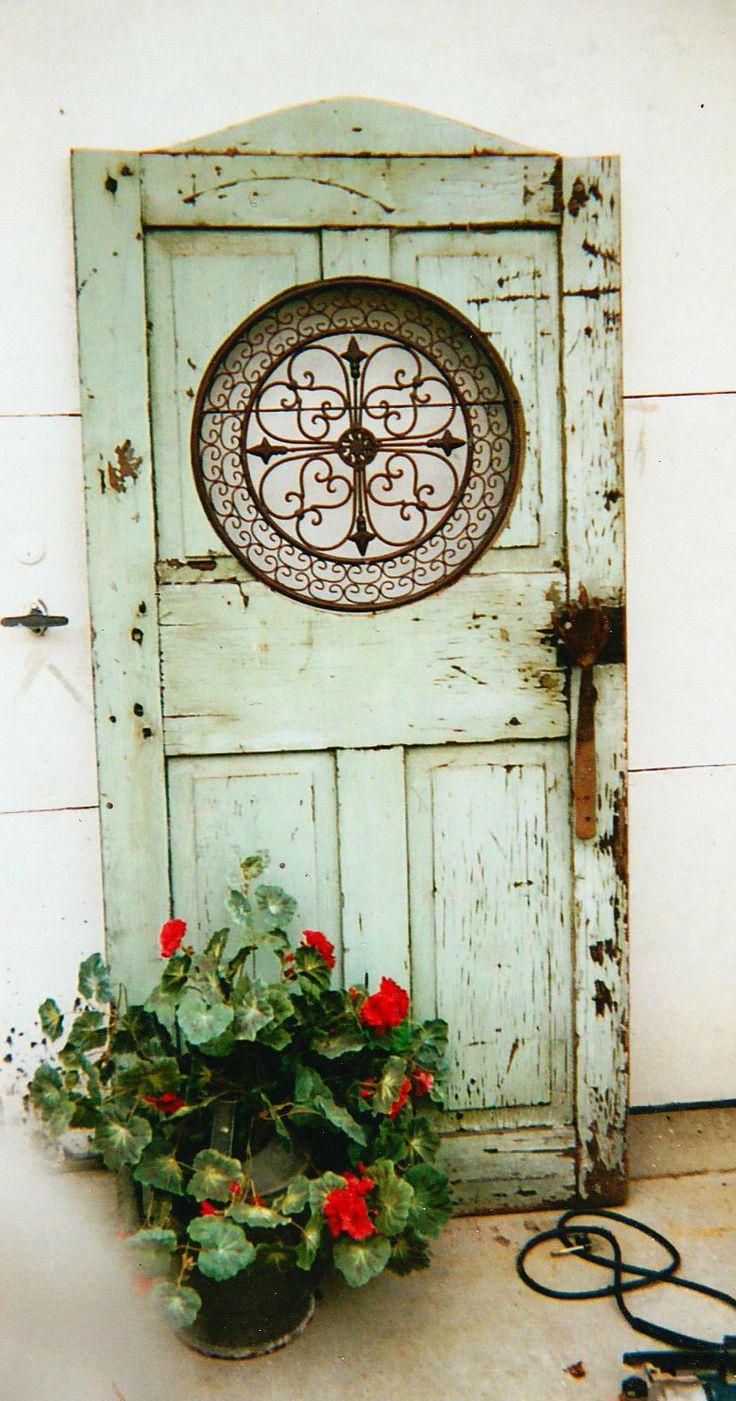 Old door repurposed with iron work (repo) from Hobby Lobby and garden tool used for handle.  2007