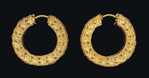 A PAIR OF ACHAEMENID GOLD EARRINGS   CIRCA 5TH CENTURY B.C.   Each constructed of gold sheet forming a large hollow hoop, rectangular in section, each corner bordered by a double row of granulation framing a thin plain wire, ornamented entirely on the sides and along the outer edge with six-petalled rosettes formed of small sheet disks, centered by a large concave disk, the plain ear wire hinged to both ends of the hoop  Each: 1 15/16 in. (4.9 cm.) long