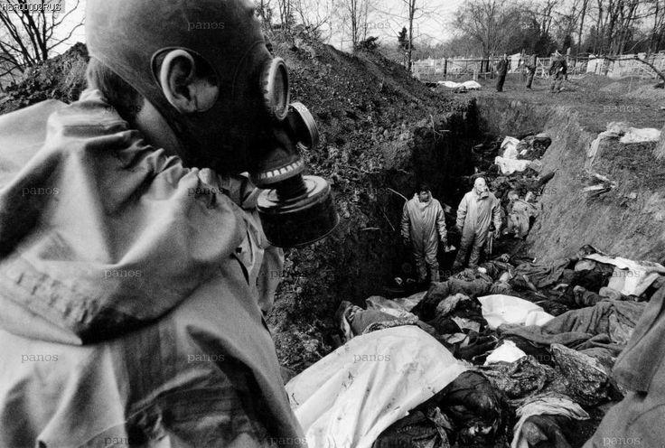Русский военный в противогазе возле траншеи с убитыми русскими войсками людьми