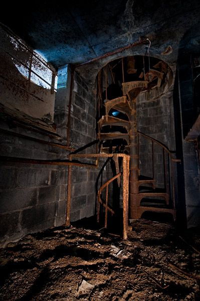 One of several spiral staircases in the basement of the Roosevelt Warehouse, where the Detroit Public School System stored unused textbooks.    The building was originally the city's main Post Office. It was connected via tunnel to Michigan Central Station across the street, where mail was delivered by train.