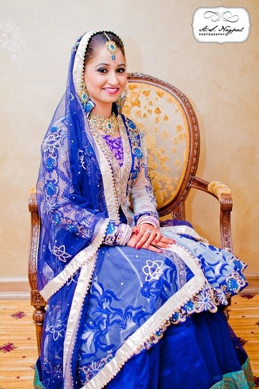 Blue long sleeved jacket lehnga with dupatta worn on head in Punjabi wedding reception via IndianWeddingSite.com