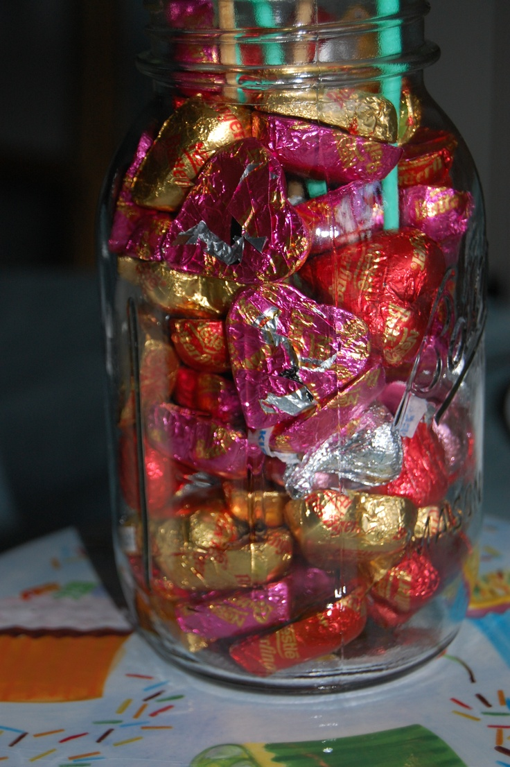 Mason jar centerpiece filled with colorfully wrapped