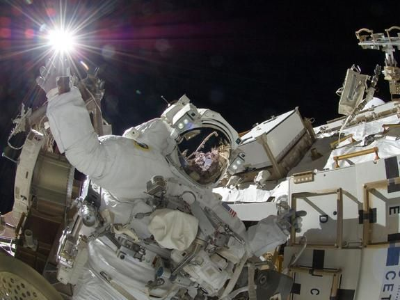 """With her crew member reflected in her visor and her hand reaching out as if to grasp the sun, astronaut Sunita Williams conducts a spacewalk outside the International Space Station. The spacewalk, which took place on Sept. 5, is the third """"EVA"""" (extravehicular activity) for the crew of Expedition 32. In a six-and-a-half hour session, Williams and astronaut Aki Hoshide of Japan completed the installation of a power unit and installed a camera on Canadarm2 the space station's robotic arm."""