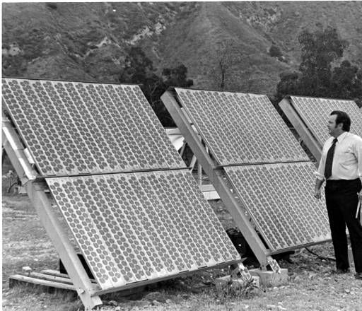 Dr. Ken Lian of Spectrolab stands by a one-kilowatt flat-plate photovoltaic array  undergoing field tests at a test farm in Sylmar, April 18, 1979. Spectrolab began as a manufacturer of optical filters and mirrors for use in the aerospace industry and provided solar arrays for Explorer 6, which in 1959 sent back the first satellite photo of Earth. Robert and Betty Franklin Collection. San Fernando Valley History Digital Library.