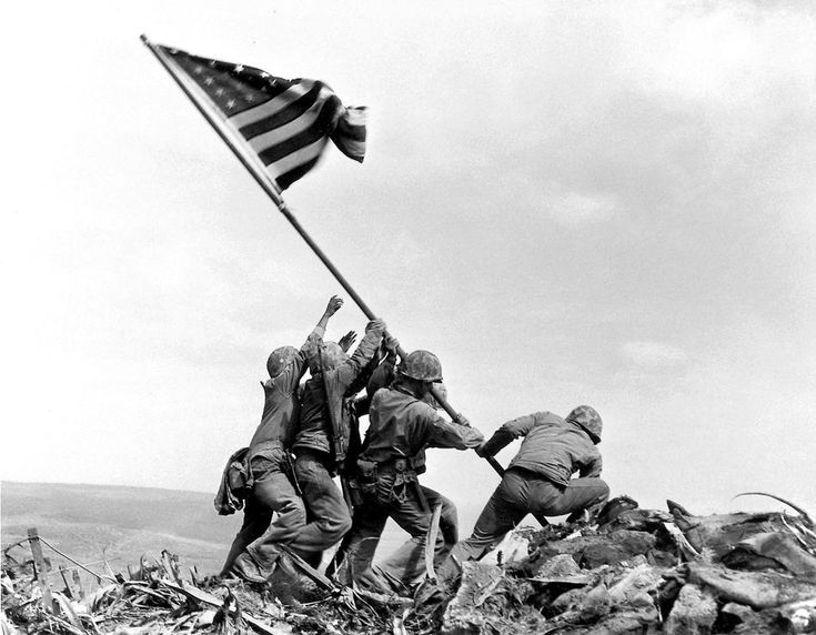 U.S. Marines of the 28th Regiment of the Fifth Division raise the American flag atop Mt. Suribachi, Iwo Jima, on Feb. 23, 1945.