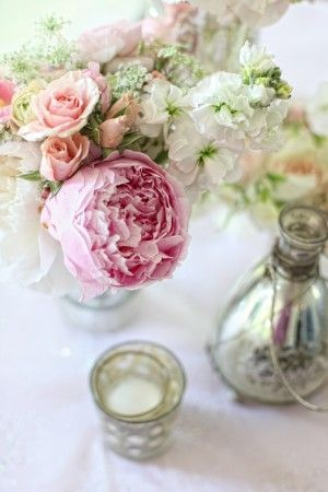 The third centerpiece design will be a white compote vase filled with blush pink hydrangeas, fuchsia peonies, Esperance roses, and blush spray roses and surrounded by mercury glass votives.