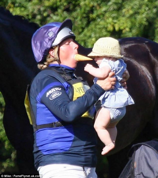 dailymail: Zara Phillips, with an ice cream cone in her mouth, holds baby daughter Mia at the Salperton Park Horse Trials, Gloucestershire, June 21 and 22, 2014