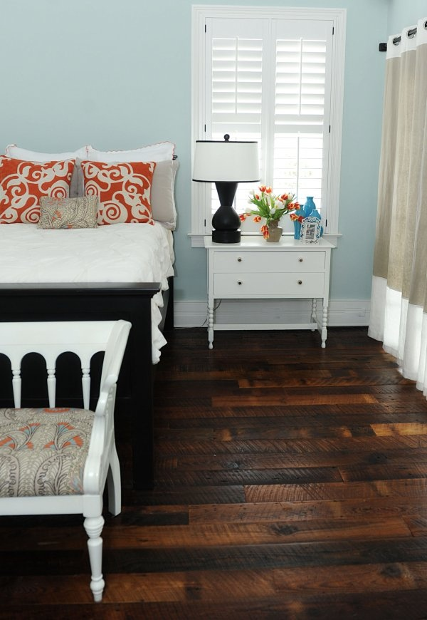 light blue orange white bedroom with dark floors by