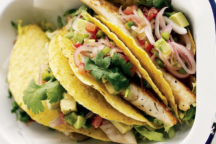 ... fish in crisp taco shells with piles of lettuce and an avocado, tomato