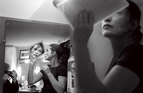 Isabelle Huppert holding mirror.