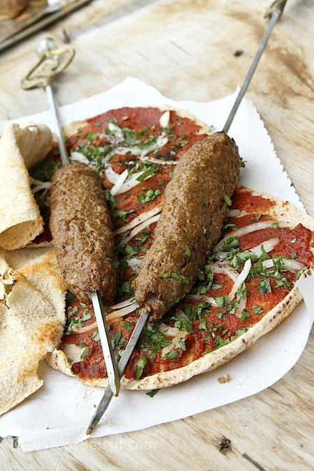 spiced ground meat kebabs on flatbread covered with tomato paste ...