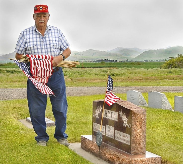 Legionnaire Larry Hyer of Lewiston pauses after placing a flag by the headstone of his father, Ira Hyer, who served in World War I. Each year, Hyer places flags on the grave markers of veterans in the Lewiston Cemetery. (Photo by Cody Gochnour)