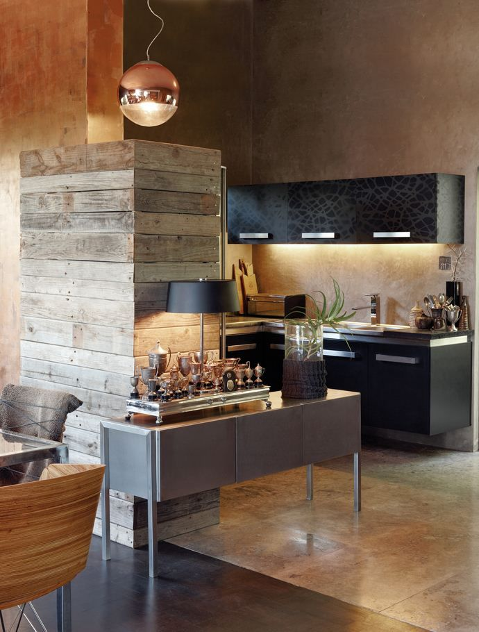 The juxtaposition of smooth and rough, shiny and textured surfaces creates visual interest in the kitchen with its metal cabinets. The trophies were found at the Milnerton Market –