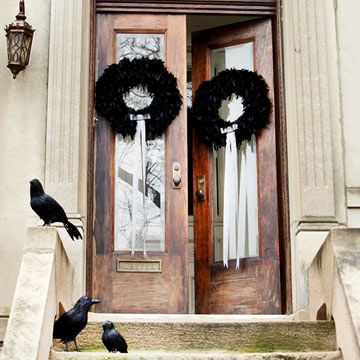 Feathered Halloween Wreaths: Symmetry is a wonderfully simple decorating tool to guide you in creating a seasonally beautiful entryway -- at Halloween or any holiday time. Here, two black feather wreaths, accented with long lengths of shimmery silver ribbon, dress up the towering front doors. Whimsical -- and not-too-spooky -- faux ravens beckon their own sort of welcome.