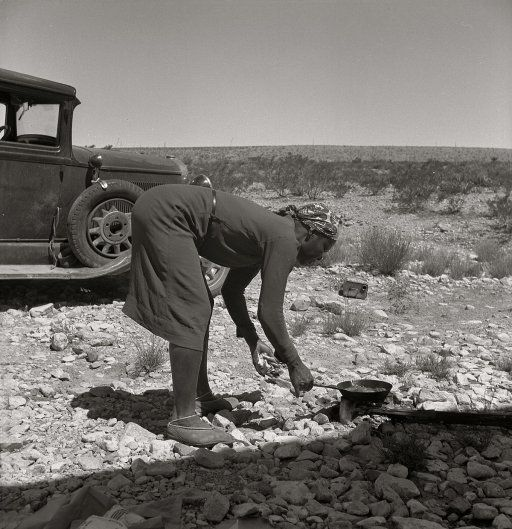 """June 1938. Outskirts of El Paso, Texas. """"Young Negro wife cooking breakfast. 'Do you suppose I'd be out on the highway cooking my steak if I had it good at home?' Occupations: hotel maid, cook, laundress."""" Medium-format nitrate negative by Dorothea Lange for the Farm Security Administration."""